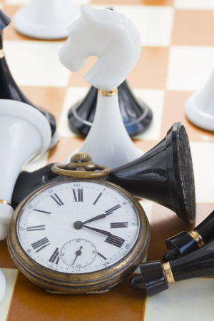 conflict theory: chess game  concept - antique clock with chess figurines Stock Photo