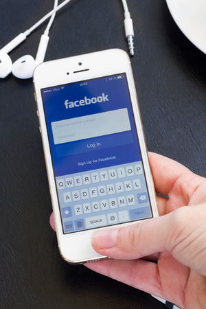 WARSZAWA, POLAND - APRIL 01, 2014: Loging in Facebook app on Iphone5s with help of finger print. Facebook the largest social network in the world. Editorial
