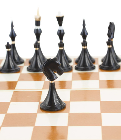 single black  knight  in front of black chess photo