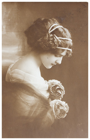 old photograph: POLAND, WARSAW - CIRCA 1913: old photo portrait of young woman with flowers. Illustrative Image, subject of human interest