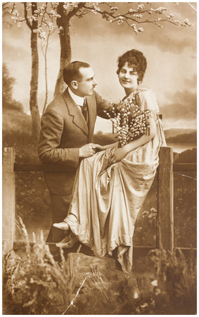 victorian girl: POLAND, WARSAW - CIRCA 1924 : old photo  of happy young romantic couple of woman and man in spring garden. Illustrative Image, subject of human interest0 Editorial