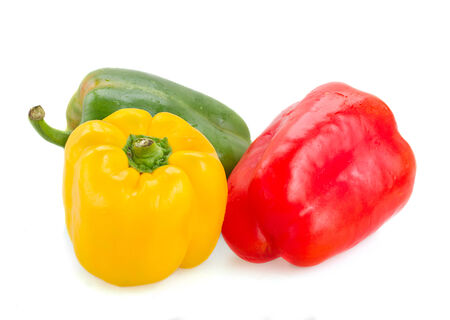 paprica: three red, green and yellow peppers isolated on white background