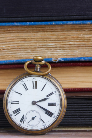 antique pocket  clock close up  on vintage  books background photo