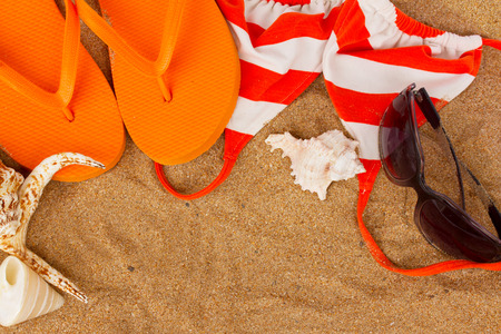 orange sandals with bikini and  shells at sand with copy space photo