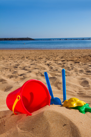 bucket with plastic beach toys  in sand on sea shore at sunny summer day photo