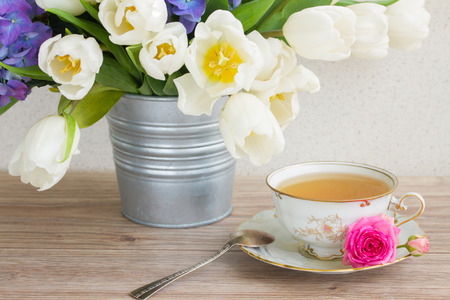 vyntage cup of tea with white tulips photo