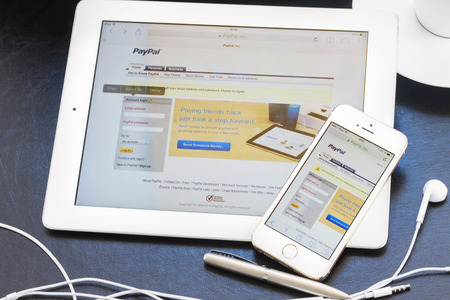 WARSZAWA, POLAND - APRIL 17, 2014. Paypal on screen of ipad and iphone 5s. PayPal is a popular and international method of money transfer via the Internet. Editorial
