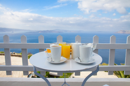 breakfast with coffee, fresh orabge juice and yogurt at morning by seaside photo