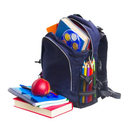 mochila: mochila escolar azul lleno de art�culos de papeler�a aislado en fondo blanco