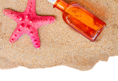 botle: red starfish ans botle with letter on beach sand border on white background