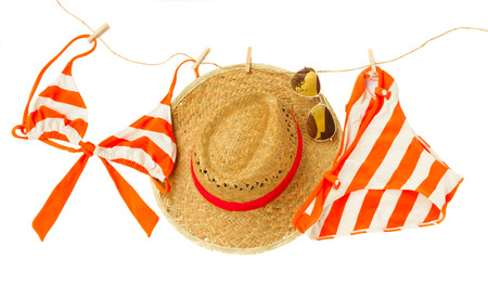 swimming suit with glasses and hat hanging on rope  isolated on white background photo