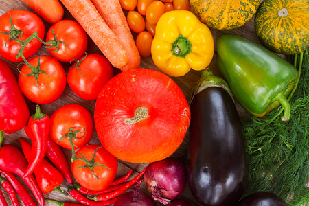 ripe of fresh vegetables in rainbow colors   - pumpkin, tomatoes,  peppers,  onions, eggplants photo