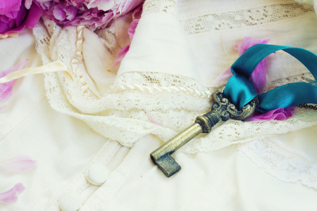 Antique key with  on vintage lace garment photo