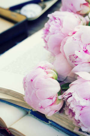 pile of vintage old books with pink peony flowers stacked on table photo