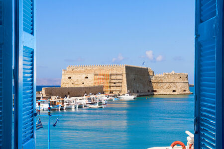 Heraklion harbour with old venetian fort through window sills, Crete, Greece photo