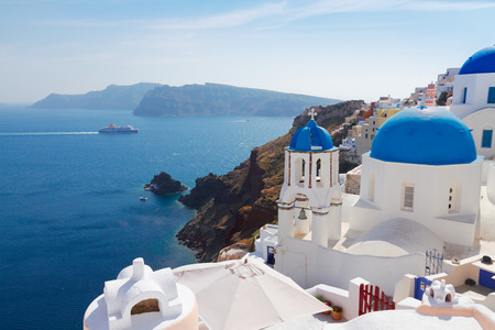 volcano caldera with blue church domes, Oia, Santorini photo
