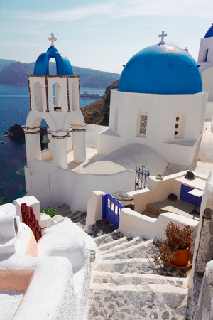 steep stairs and classical church with blue domes , Oia, Santorini, Greece photo