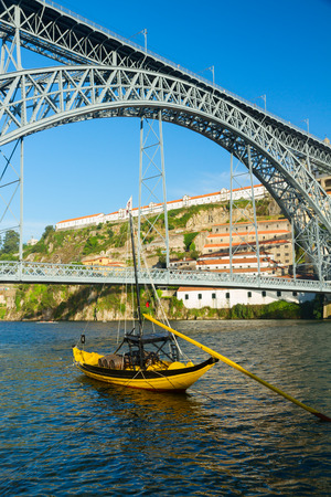 rabelo: traditional rabelo boat and bridge of Dom Luis I at sunny day in old Porto, Portugal