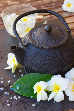 Spa and wellness setting with natural sea salt,flowers and tea photo