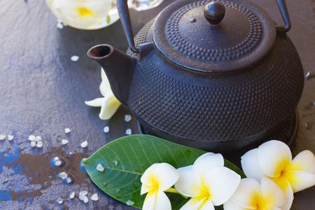 Spa and wellness setting with natural sea salt, frangipani flowers and tea photo