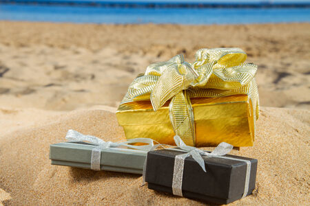 beach wrap: pile of christmas gifts on beach  with golden sand