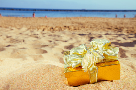 beach wrap: golden christmas gift on beach  with golden sand