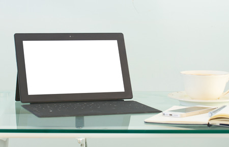 Modern working place with tablet  and coffee mug on glass  table photo