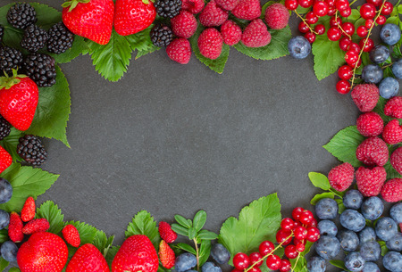 frame of fresh berries with green leaves on black stone background photo