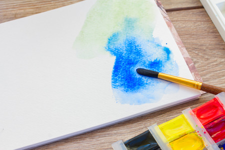 canva: white canva with watercolor stroke and brush on table
