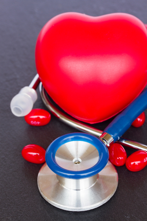 modern stethoscope with red heart and pills on black table photo