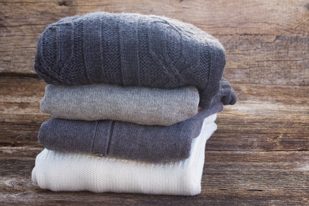 stack of folded woolen clothes on wooden background Stock Photo - 33034963
