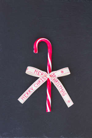 candy stick: candy stick with merry christmas bow on black background
