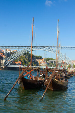 rabelo: traditional two rabelo boats and bridge of Dom Luis I at sunny day in old Porto, Portugal Stock Photo