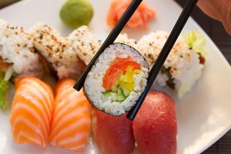 lunch with japaneese  sushi dish  with roll in chopsticks close up Banco de Imagens