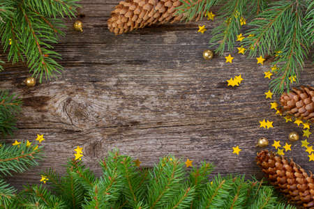 green frame: christmas  fir tree with cones frame on wooden background