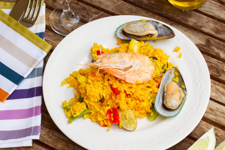 marisco: Paella, traditional spanish dish  served in  white plate on wooden table