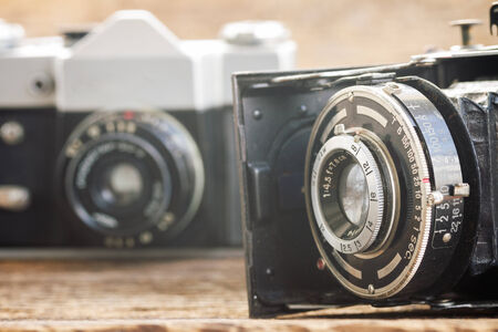 two vintage photo cameras on wooden background photo