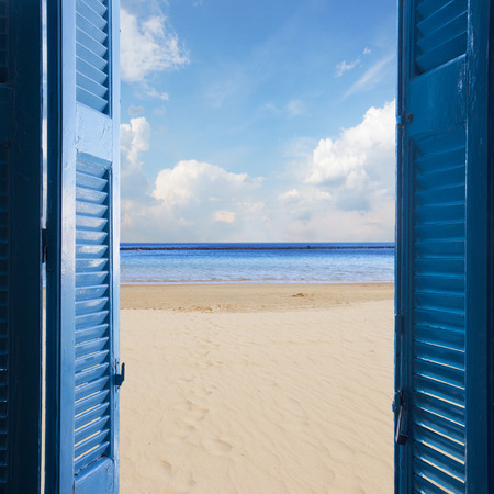 new beginings concept  - open blue door to sandy beach and sky with sunshine