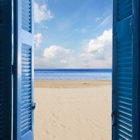 nieuwe beginings concept - open blauwe deur naar zandstrand en de hemel met de zon