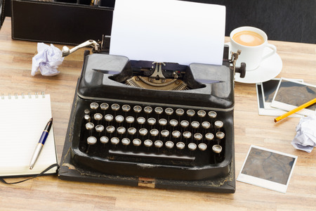 black vintage typewriter with blank  white page on working table photo