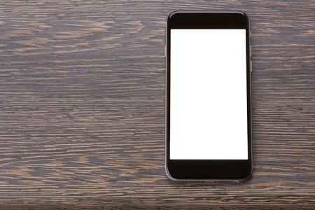 現代の黒いスマート フォン画面にコピー スペースを木製のテーブルを置くこと 写真素材