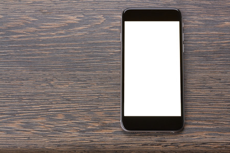 modern black smartphone laying on wooden table with copy space on screen