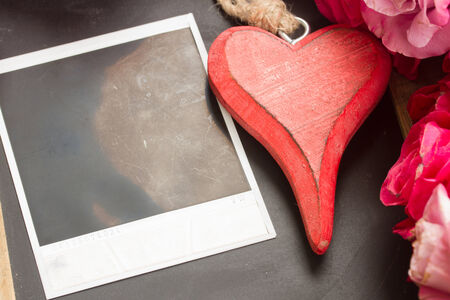 blank instant  on black   table with heart and flowers photo