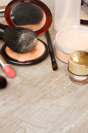 Basic make-up products - foundation, powder and lipstick on wooden background with copy space photo