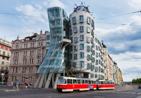 PRAGUE - AUGUST 20: Dancing House with passing tram on August 20, 2014 in Prague. The Dancing Housewas designed 1992 by Vlado Milunic and Frank Gehry and completed 1996