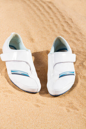 white sneakers in sand photo