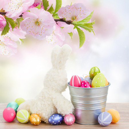 easter rabbit  with metal pot full of  eggs in  spring blossoming  garden photo