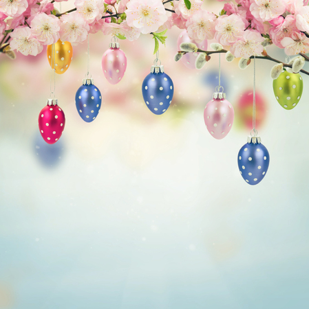Colorful hanging easter eggs with cherry flowers  on blue  background, retro toned photo