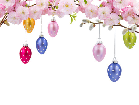 Colorful hanging easter eggs with cherry flowers border on white bacjground photo