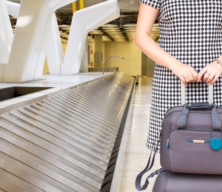woman with suitcases close up close to airport luggage belt photo